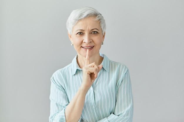 Atractiva empresaria madura con peinado de duendecillo posando aislado, sosteniendo el dedo índice levantado, con muchas grandes ideas. hermosa mujer de mediana edad levantando el dedo índice para llamar la atención Foto gratis