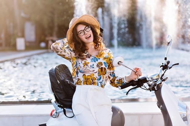 Atractiva estudiante posando juguetonamente con sombrero nuevo tocando su scooter frente a la fuente Foto gratis