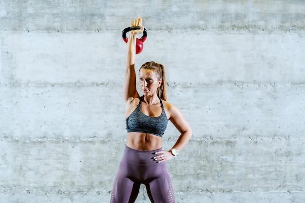 Atractiva joven deportista caucásica en ropa deportiva con cola de caballo de pie con una mano en la cadera y levantando la campana de la caldera. Foto Premium