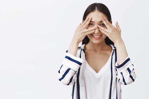Atractiva joven encantadora y amigable con blusa a rayas, cubriéndose los ojos con las palmas y mirando a través de los dedos, sonriendo ampliamente Foto gratis
