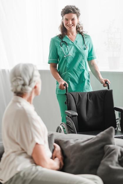 Atractiva joven enfermera mujer llevando silla de ruedas a paciente senior Foto gratis