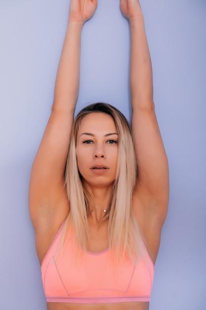 Atractiva joven mujer sexy en ropa deportiva posando sobre fondo gris. modelo femenino rubio delgado y saludable en estudio posando para la cámara. Foto Premium