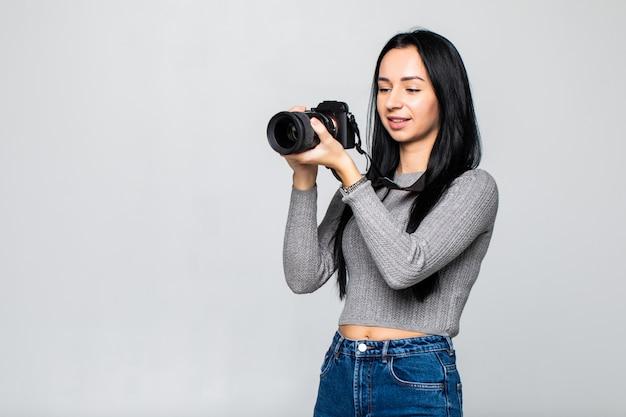 Atractiva morena apunta su cámara. componer una fotografía en estudio, aislado en la pared gris Foto gratis