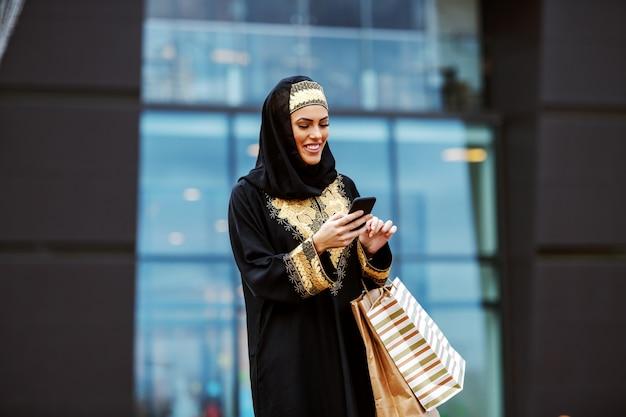 Atractiva mujer árabe en ropa tradicional de pie frente al centro comercial con bolsas de compras en las manos y usando teléfonos inteligentes para leer o enviar mensajes. Foto Premium