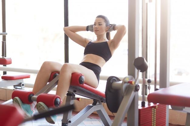 La atractiva mujer atlética bombea el simulador de presión en el gimnasio deportivo, tonifica los músculos, levanta la parte superior del cuerpo, desarrolla la definición de los músculos Foto gratis