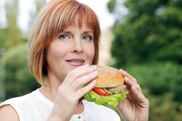 Atractiva mujer comiendo en un parque Foto gratis