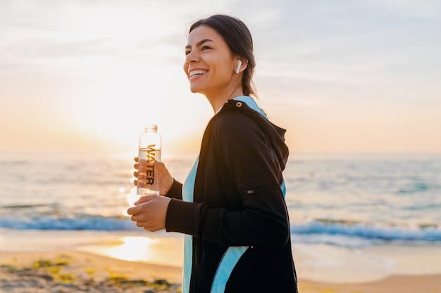 Atractiva mujer delgada haciendo ejercicios deportivos en la playa del amanecer de la mañana en ropa deportiva, agua potable sedienta en botella, estilo de vida saludable, escuchando música en auriculares inalámbricos, sonriendo feliz Foto gratis