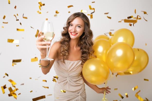 Atractiva mujer joven y elegante celebrando el año nuevo, bebiendo champán sosteniendo globos de aire, confeti dorado volando, sonriendo feliz, blanco, aislado, vestido de fiesta Foto gratis