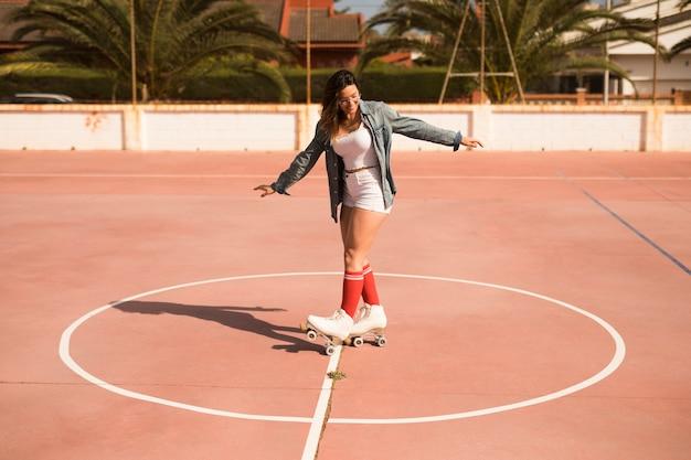 Una atractiva mujer joven que llevaba patinaje sobre ruedas en la cancha Foto gratis