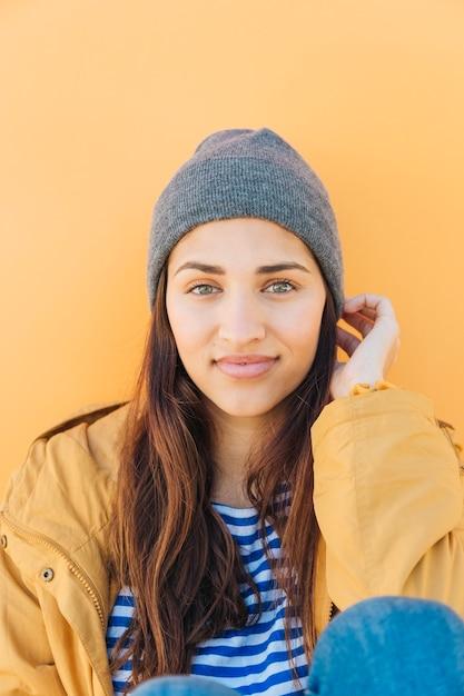 Atractiva mujer joven sentada contra el fondo amarillo liso con sombrero de punto Foto gratis