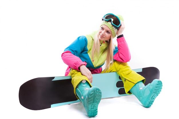 Atractiva mujer joven en traje de esquí y gafas de esquí sentarse en snowboard Foto Premium