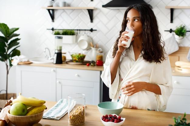 La atractiva mujer mulata sonríe está bebiendo leche cerca de la mesa con frutas frescas en la moderna cocina blanca vestida con ropa de dormir con el pelo suelto y mirando a la derecha Foto gratis