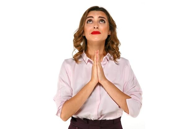 Atractiva mujer de negocios rezando, deseando y esperando algo Foto gratis