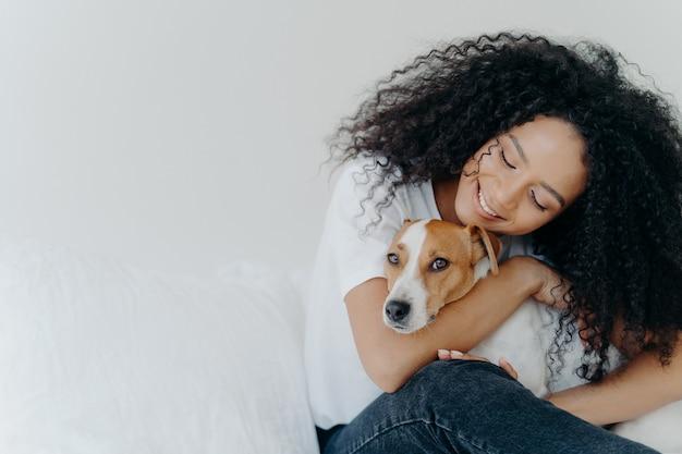 Atractiva mujer con peinado afro rizado, caricias y mascotas perro con sonrisa, expresa amor, disfruta de un acogedor ambiente doméstico Foto Premium