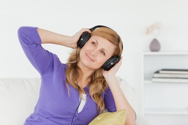 064024de93e Atractiva mujer pelirroja escuchando música y disfrutando el momento mientras  está sentada en un sofá | Descargar Fotos premium