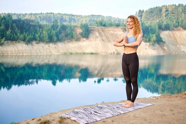 Atractiva mujer rizada pelirroja o modelo practicando yoga al aire libre Foto Premium