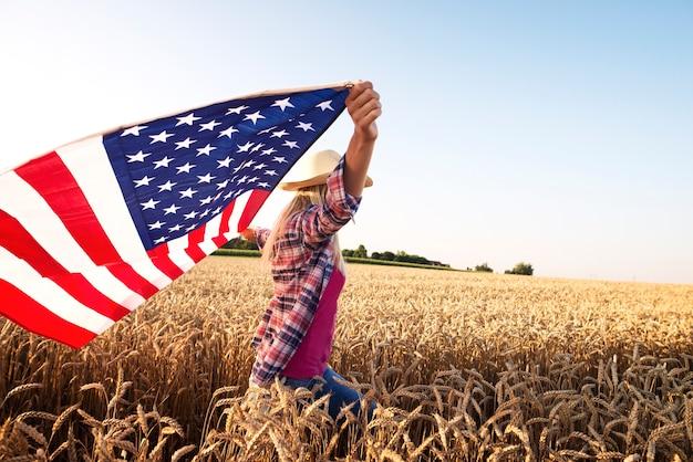 Atractiva mujer rubia caminando por el campo de trigo y sosteniendo la bandera ondeante de estados unidos Foto gratis