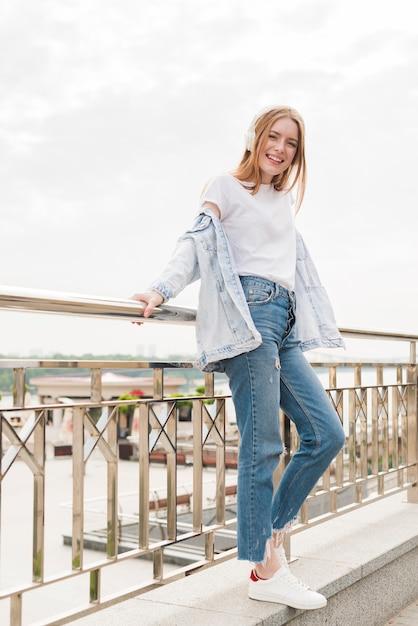 Atractiva mujer sonriente apoyada en la barandilla del puente y escuchando música. Foto gratis
