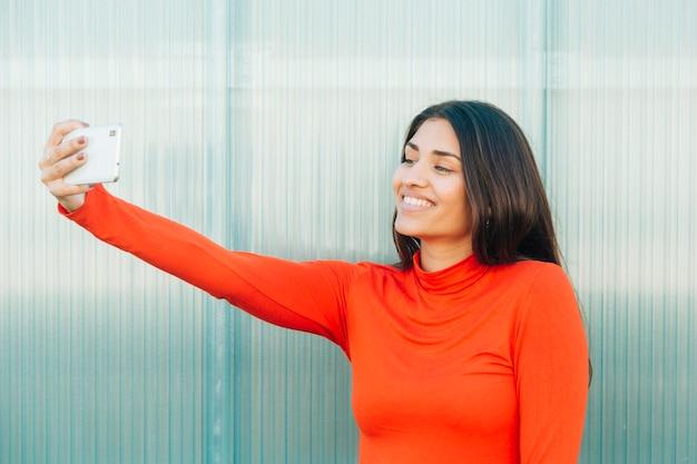 Atractiva mujer sonriente tomando selfie con celular Foto gratis