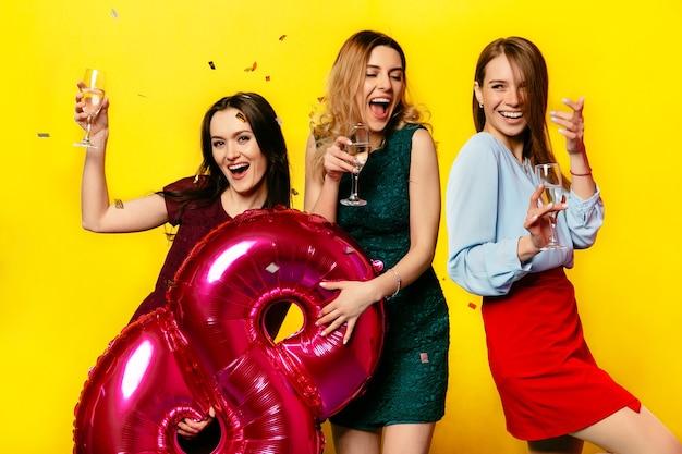 Atractivas mujeres jóvenes sonrientes con copas de champán Foto gratis