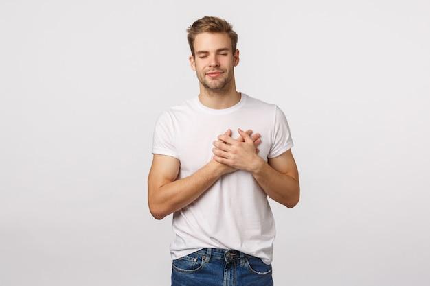Atractivo hombre rubio con barba en camiseta blanca con las manos en el corazón Foto Premium
