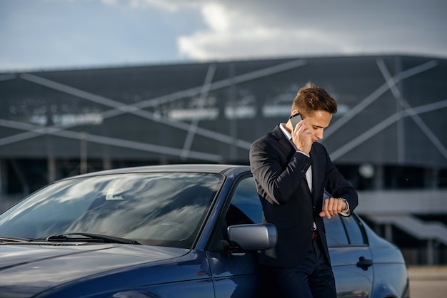 Atractivo joven empresario exitoso en un traje de negocios y ver en la mano hablando por teléfono inteligente cerca de su automóvil Foto Premium