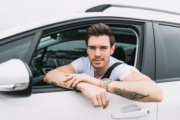 Un atractivo joven mirando por la ventana del coche Foto gratis