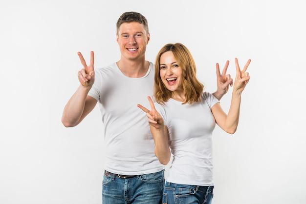 Un atractivo joven pareja mostrando signo de victoria contra el fondo blanco Foto gratis