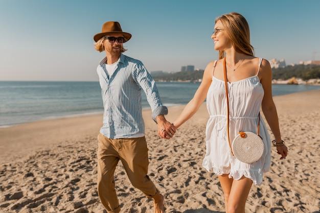 Atractivo joven sonriente feliz con sombrero y mujer rubia en vestido blanco corriendo juntos en la playa Foto gratis