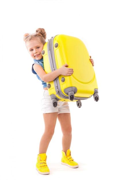 Attructiva niña linda con camisa azul, pantalones cortos blancos y gafas de sol con maleta amarilla Foto Premium