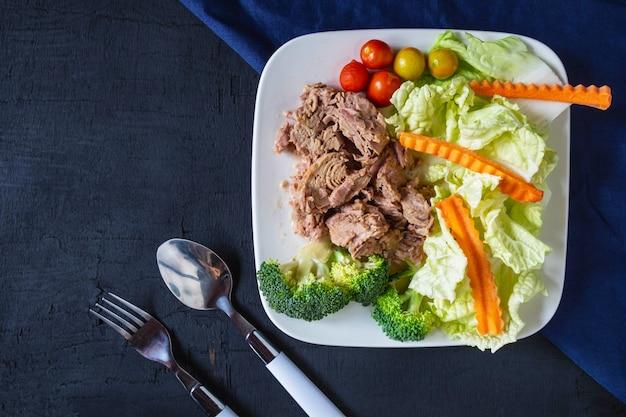 Atún y verduras saludables en un plato sobre la mesa. Foto Premium