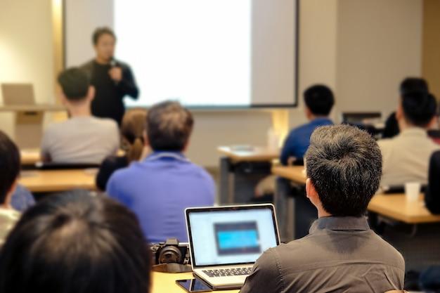 Audiencia escuchar al orador que está parado en frente de la sala en la sala de conferencias Foto Premium