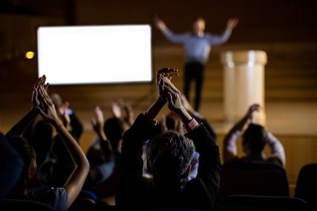 Audiencia que aplaude al orador después de la presentación de la conferencia Foto gratis