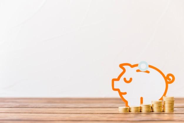 Aumento de monedas apiladas delante de piggybank en superficie de madera Foto gratis