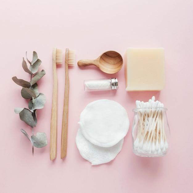 Auriculares de bambú, cepillos de dientes, hilo natural, almohadillas para desmaquillar algodón, champú y barras de jabón. Foto Premium