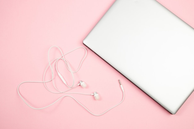 Auriculares y computadora portátil atados con alambre blancos en fondo aislado rosa. vista superior. aplanada bosquejo Foto Premium
