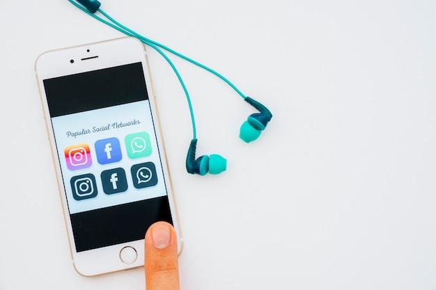 Auriculares y dedo tocando el móvil con aplicaciones populares Foto gratis