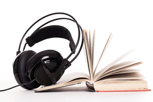 Auriculares y libro sobre un fondo blanco. Foto gratis