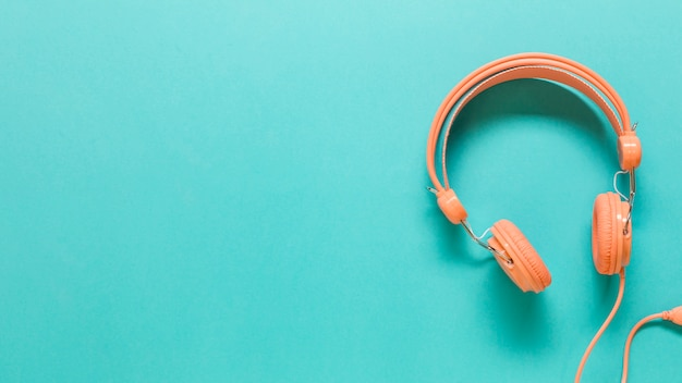 Auriculares naranjas en superficie coloreada Foto gratis