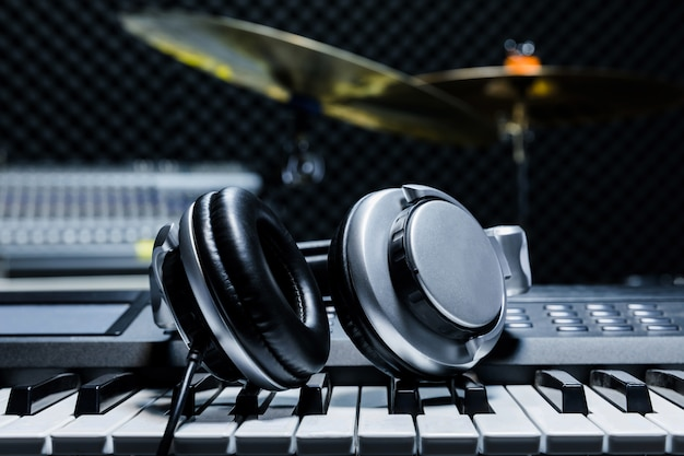 Auriculares sobre fondo de piano eléctrico por el fondo de instrumentos musicales. Foto Premium
