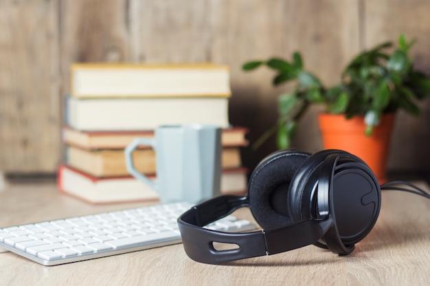 Auriculares, teclado, pila de libros y taza en el escritorio de la oficina. concepto de oficina, día de trabajo, pago por hora, horario de trabajo, trabajo en un centro de llamadas. Foto Premium