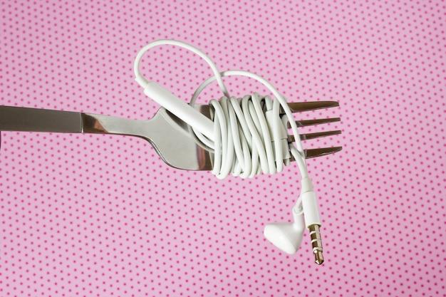 Auriculares y tenedor blancos sobre un fondo rosa con lunares, primer plano Foto Premium