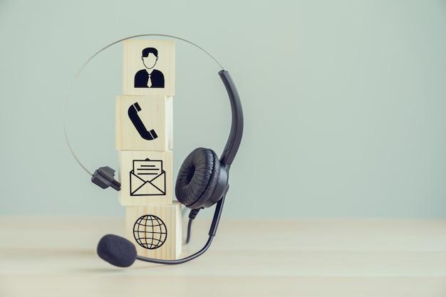 Auriculares voip y comunicación de iconos en el bloque de madera. Foto Premium