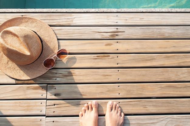 Autofoto de pies descalzos sobre suelo de madera con gorra y gafas de sol. concepto de verano Foto Premium