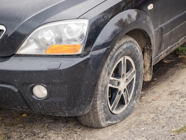 Un automóvil negro con una rueda delantera desinflada. Foto Premium