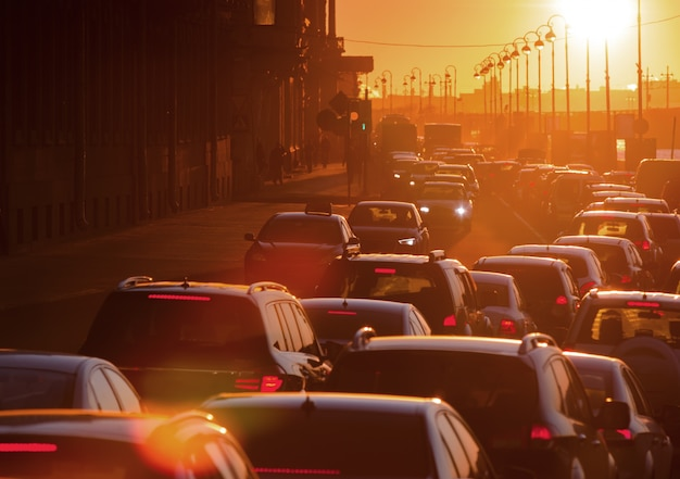 Los autos se encuentran en un embotellamiento durante una hermosa puesta de sol dorada en una gran ciudad. Foto Premium