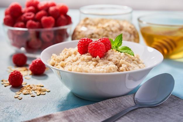 Avena casera con frambuesas frescas y miel orgánica para el desayuno en turquesa. Foto Premium