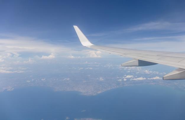 Avión ala vista por la ventana el fondo del cielo nublado Foto Premium