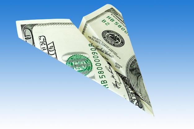 Avión de dinero sobre un fondo azul. Foto Premium