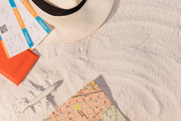 Avión y entradas con sombrero y mapa sobre arena. Foto gratis